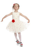 Elegant Princess white dress. Delicate little Princess dressed in a white dress with a red flower at the waist . The girl moves in front of the camera waving Royalty Free Stock Image