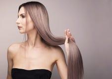 Elegant profil av en kvinna med långt purpurfärgat hår royaltyfri foto