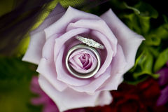 Elegant Promise. Beautiful diamond wedding ring and a wedding band nestled in a purple rose Royalty Free Stock Photos
