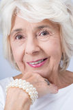 Elegant and proud woman from aristocracy. Pretty older elegant and proud woman from aristocracy wearing expensive jewelry royalty free stock photography