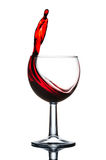 Elegant pure wineglass with wave of brightly red wine isolated on white royalty free stock photo