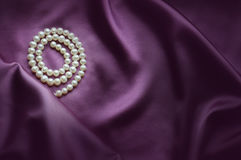 Elegant purple background with silk and pearls. Closeup stock image