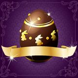 Elegant purple banner with chocolate egg. High gloss design with a gold banner wrapped around a decorated chocolate egg. Graphics are grouped and in several Stock Image