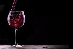 Elegant rött vinexponeringsglas i svart bakgrund Royaltyfria Bilder