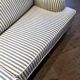 Elegant randig soffa på mörkt trägolv Arkivbild
