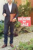 Elegant real estate agent. Close-up of elegant real estate agent with leather notebook standing next to house for sale stock photography