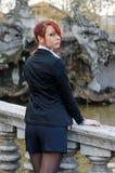 Elegant red-head girl outdoors against stone banister Stock Photography