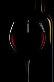 Elegant red wine glass and a wine bottles in black background Royalty Free Stock Photography