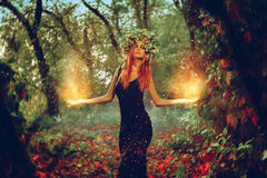 Elegant redhair girl witch conjures in the magic forest. Outdoors Royalty Free Stock Photography