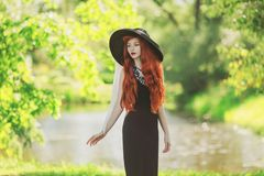 Elegant Redhead Girl In Black Retro Dress On Nature Background. Beautiful Vintage Woman. Elegant Lady In Retro Hat. Fashion Stock Photo