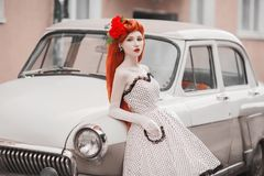 Elegant Redhead Girl In White Retro Dress On Car Background. Beautiful Vintage Woman With Red Lips. Lady In Long Retro Gloves. Royalty Free Stock Photos