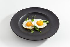 Fried Eggs Decorated with Fresh Spinach Leaves and Young Pea Shoots. Elegant Restaurant Plate of Fried Eggs Decorated with Fresh Spinach Leaves and Young Pea royalty free stock image
