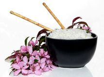 Elegant Rice. A bowl of rice in a black bowl elegantly surrounded by pink flowers royalty free stock photography