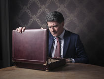 Elegant rich man opening his briefcase. Elegant rich man with a worried expression looking inside his briefcase stock images