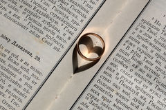 Elegant ring on bible. One elegant golden wedding ring jewel having heart shaped shadow symbol of love and unity on background of white page of bible book Stock Photo