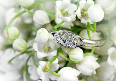 Elegant ring and lily of the valley. Elegant jewelry ring with brilliant and spring natural flowers Royalty Free Stock Image