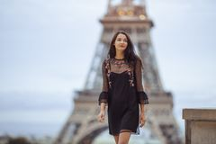 Parisian woman near the Eiffel tower in Paris, France. Elegant romantic Parisian woman in black sexy dress with flowers walking near the Eiffel tower at Royalty Free Stock Photos