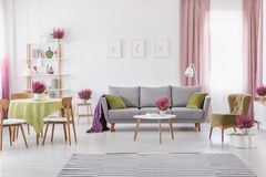 Elegant daily room with round table with wooden chairs and grey sofa with olive green pillows, stylish armchair next to it. Real photo stock photo