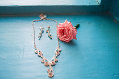 Elegant rose with necklace and earrings on a blue Stock Photo