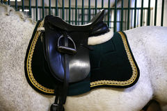 Elegant saddle for riders on horseback in the barn. Beautiful leather saddle for equestrian sports on horseback Royalty Free Stock Images