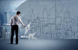 Elegant salesman repainting the city on wall Stock Photos