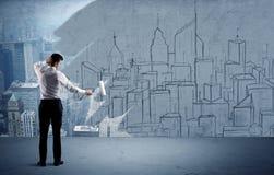 Elegant salesman repainting the city on wall Stock Image