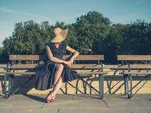 Elegant sammanträde för den unga kvinnan parkerar på bänken arkivfoton