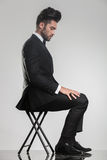 Elegant sammanträde för ung man på en stol som ner ser Royaltyfri Foto