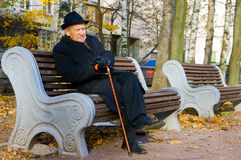 Elegant Senior. Portrait of an old man in a hat sitting on a bench Stock Photo