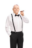Elegant senior gentleman smoking a cigar Stock Photo