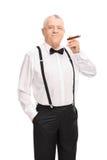 Elegant senior gentleman smoking a cigar Stock Photo