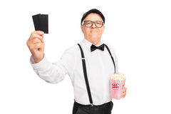 Elegant senior holding two tickets. Elegant senior gentleman holding a box of popcorn and two tickets isolated on white background Stock Photography