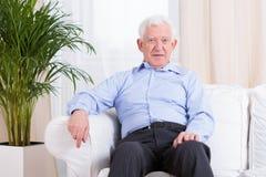 Elegant senior man. Sitting in the armchair royalty free stock photography