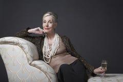 Elegant Senior Woman On Chaise Lounge With Champagne. Portrait of an elegant senior woman sitting on chaise lounge with champagne against black background royalty free stock photos