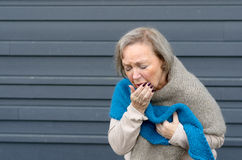 Elegant senior woman coughing into her hand. While clutching her chest in a concept of seasonal bronchitis or influenza and medical healthcare, grey metal royalty free stock images