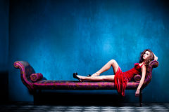 Elegant sensual woman. Sensual elegant young woman in red dress on recamier indoor shot Stock Images