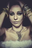 Elegant and sensual woman with golden light, gold and silver jew Royalty Free Stock Images