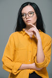Elegant sensual woman posing in yellow blouse and stylish glasses. Isolated on grey Royalty Free Stock Photos