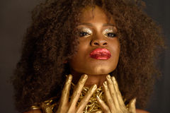Elegant serious African or black American woman wearing gold makeup and accessories posing touching her chin with hands Royalty Free Stock Photos