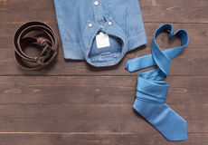 Elegant set: brown leather belt, blue shirt and blue necktie on Stock Photography