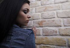 Elegant sexy brunette in jeans over brick wall Stock Photography
