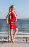An elegant and female on a blue sea background. The confident lady in a bright red dress with a cleavage near the sea. stock photography