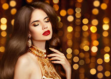 Elegant sexy girl portrait in gold. Makeup. Fashion earrings jew Stock Photo