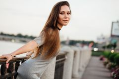 Elegant girl walks along the promenade. Beautiful handrails, forged. Long hair. Boots. leaned back and posed. Choker stock photos