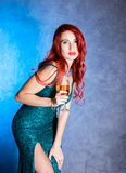 Elegant woman with big boobs in tight blue dress holding wineglass with champagne.  royalty free stock photography