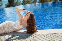 Elegant woman in fashion dress lying by blue swimming pool. stock photos