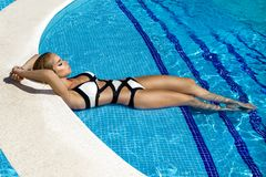 Elegant sexy woman in luxury bikini on the sun-tanned slim and shapely body is posing near the swimming pool - Image royalty free stock photo