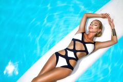 Elegant sexy woman in luxury bikini on the sun-tanned slim and shapely body is posing near the swimming pool. Sunbathing By stock photo