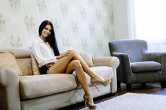 Elegant and sexy woman sitting on a sofa in a luxurious room Stock Image