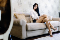 Elegant and sexy woman sitting on a sofa in a luxurious room Stock Photography